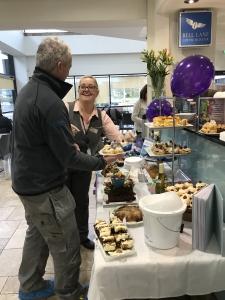 q cafe staff member serving cake sot a customer