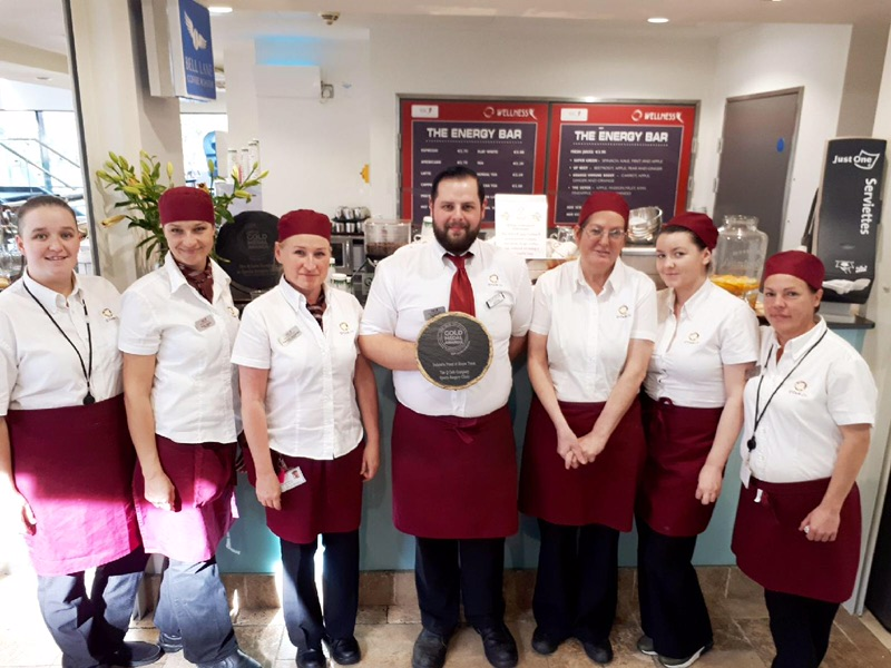 q cafe company sports surgery team posing with the gold medal award