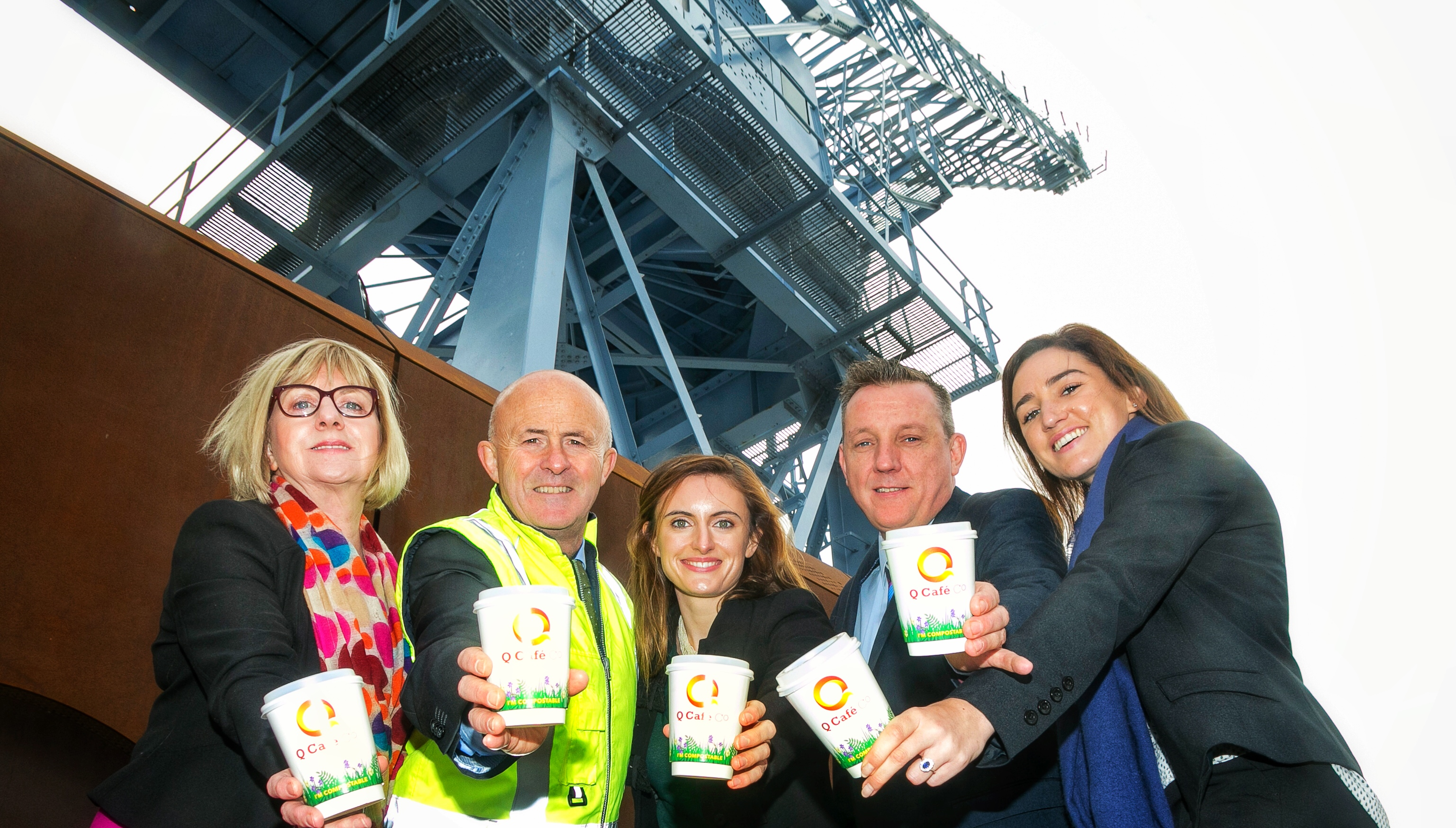 group holds compostable cup in front of Dublin Port crane