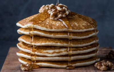 Stack of pancakes with syrup being poured over them and few walnuts on top