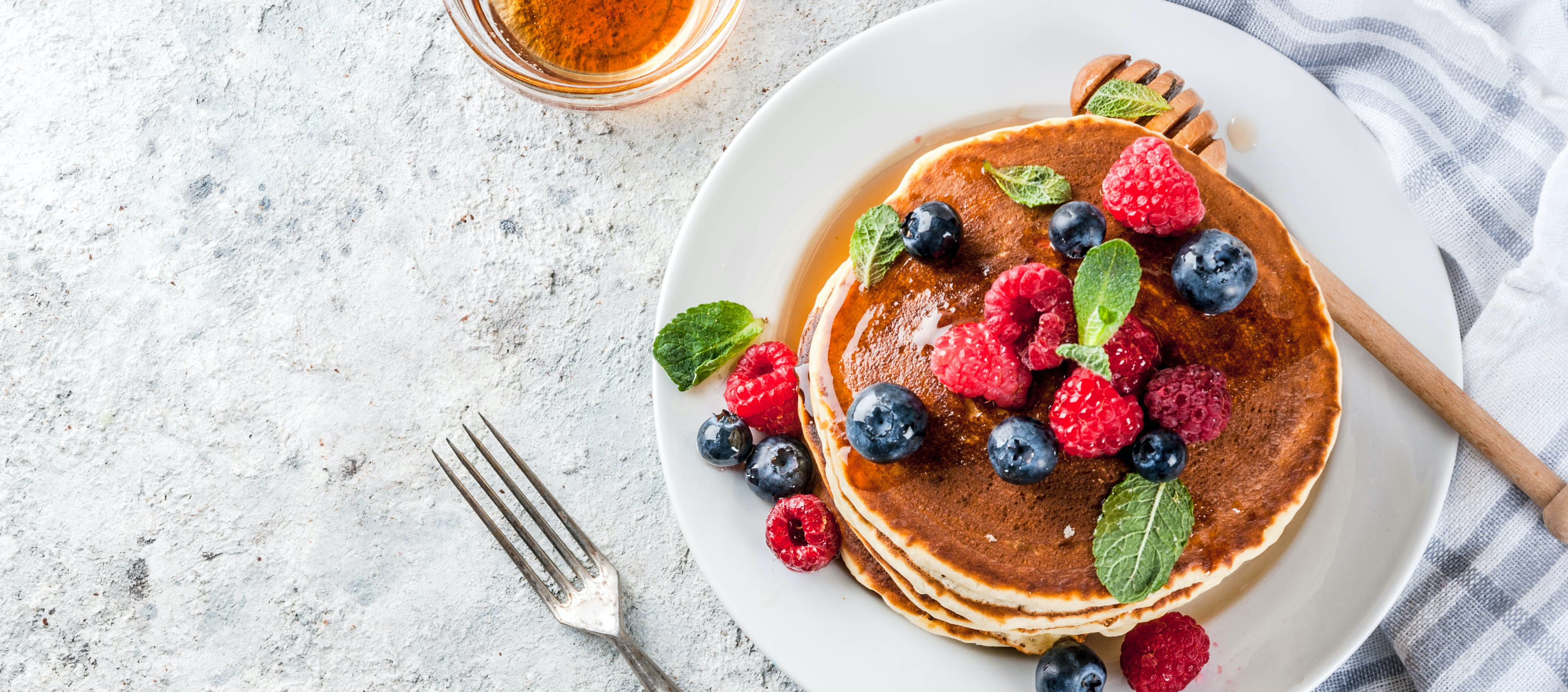 stack of pancakes on on a plate topped with berries and mint. Image portrays a healthy plate of pancakes.
