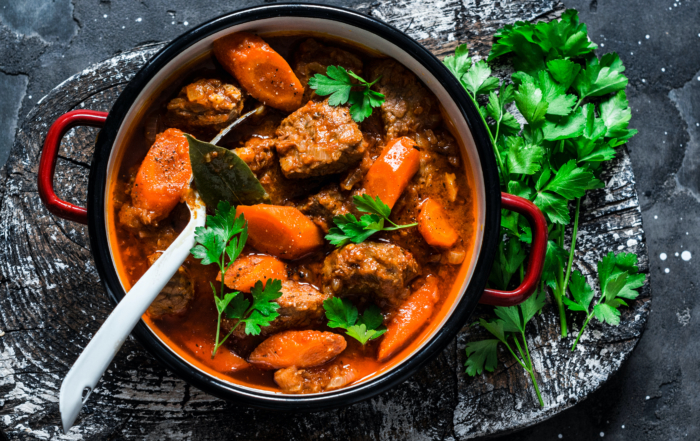 picture of beef stew in a bowl with a fork and some herbs