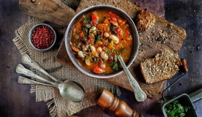 Picture of chunky soup on a wooden board with brown bread and spoons.
