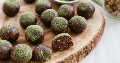 Chocolate energy balls, dusted with matcha powder on a board.