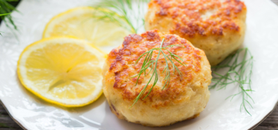 two fish cake son a white plate with dill and lemon