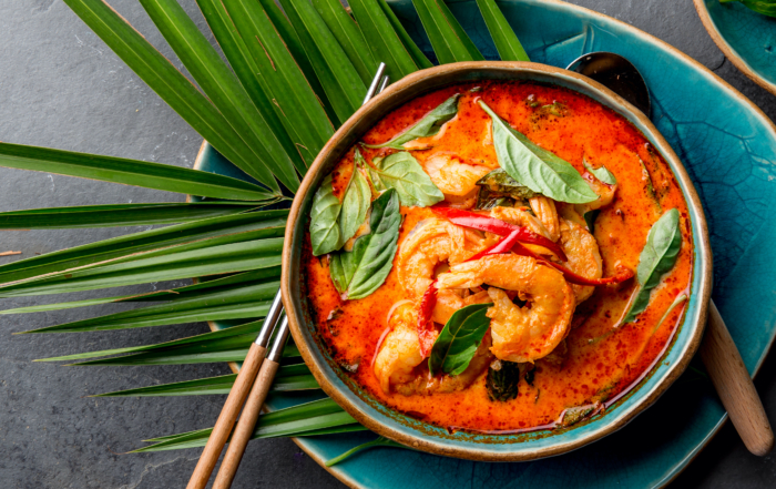overhead picture of prawn laska in a bowl. Sitting on top of a palm leaf