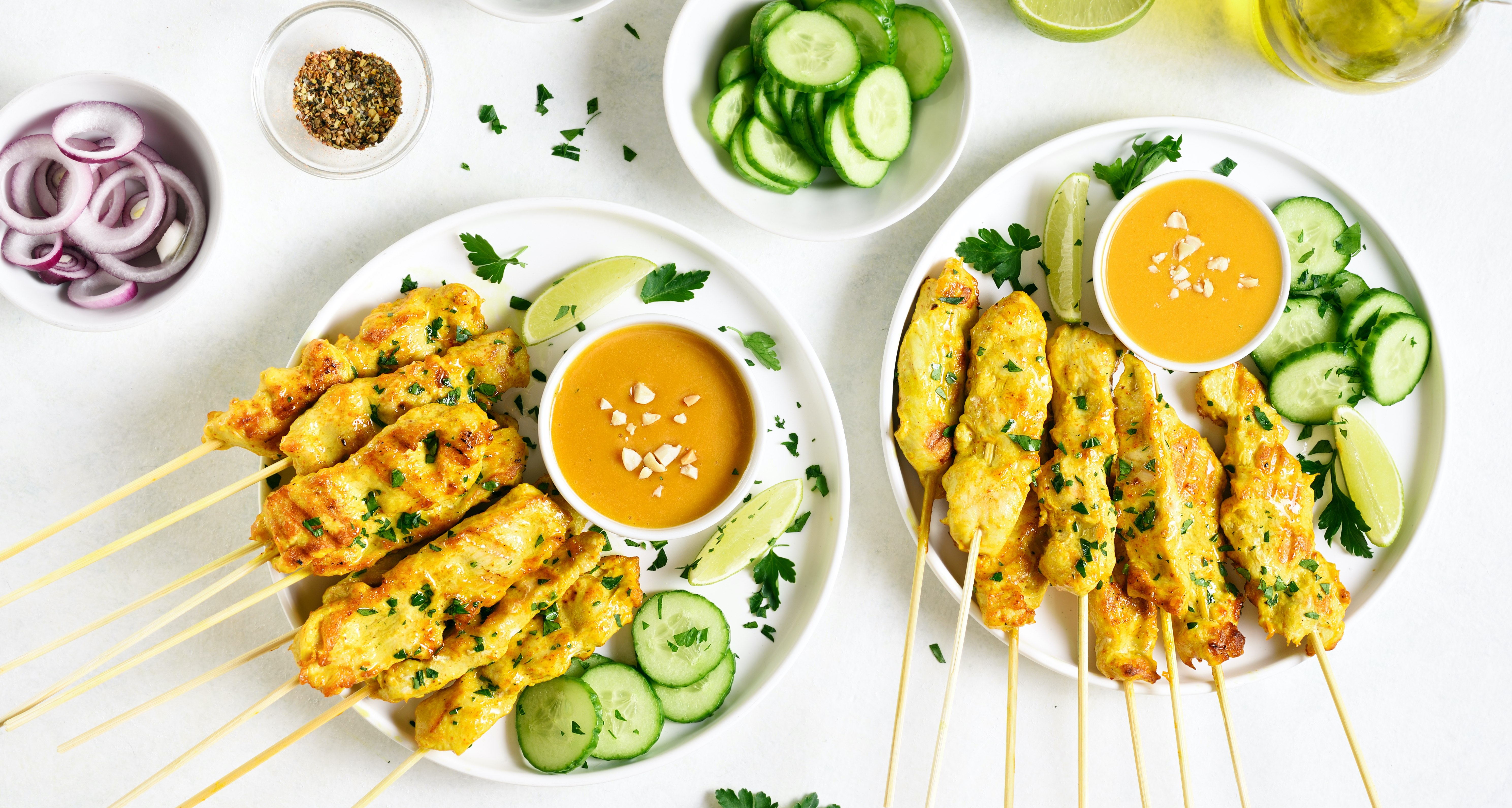 chicken seekers on a white plate with peanut satay sauce in small bowls
